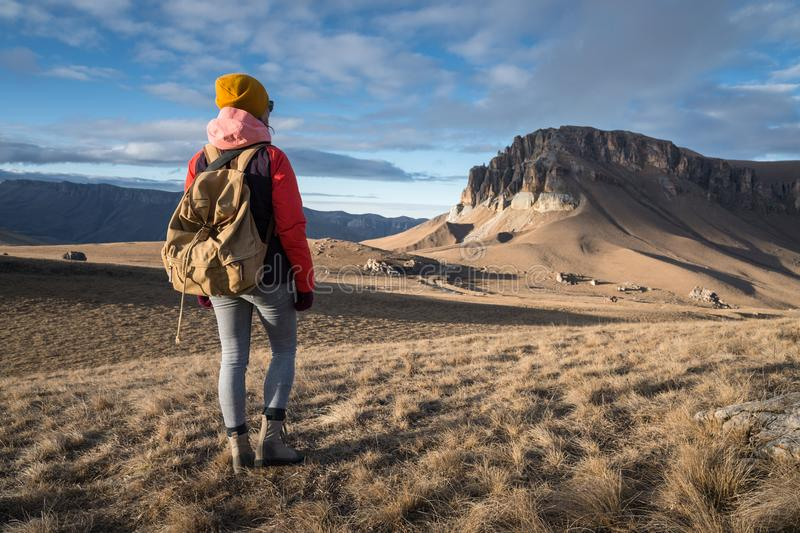 Le portrait de derrière d'une voyageuse de fille dans une veste avec une capsule et un sac à dos se tient sur le fond d'une épopé photo stock