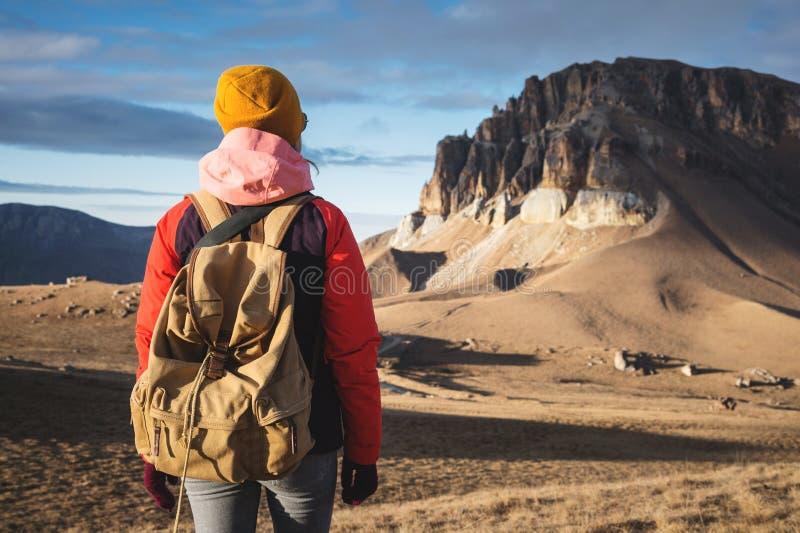 Le portrait de derrière d'une voyageuse de fille dans une veste avec une capsule et un sac à dos se tient sur le fond d'une épopé images stock