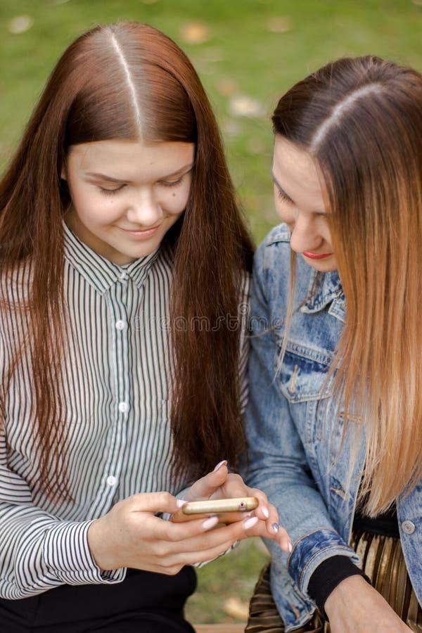 Le portrait de deux belles jeunes filles examinent le téléphone, se reposant sur un banc en parc d'automne photos libres de droits