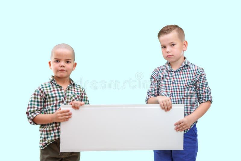 Le portrait de deux garçons tenant le blanc se connectent le fond d'isolement photos stock