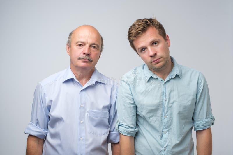 Le portrait de deux hommes mûrs avec alimentée l'expression ennuyée, regards contrarient Le père et le fils sont fatigués et ennu photos libres de droits