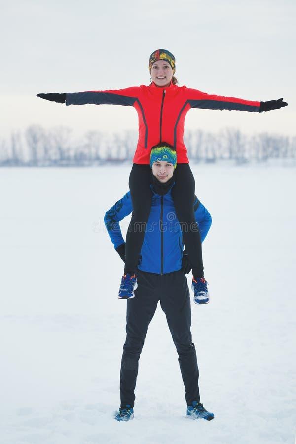 Le portrait de deux jeunes sportifs de sourire en hiver, la fille se repose sur les épaules d'un type images stock