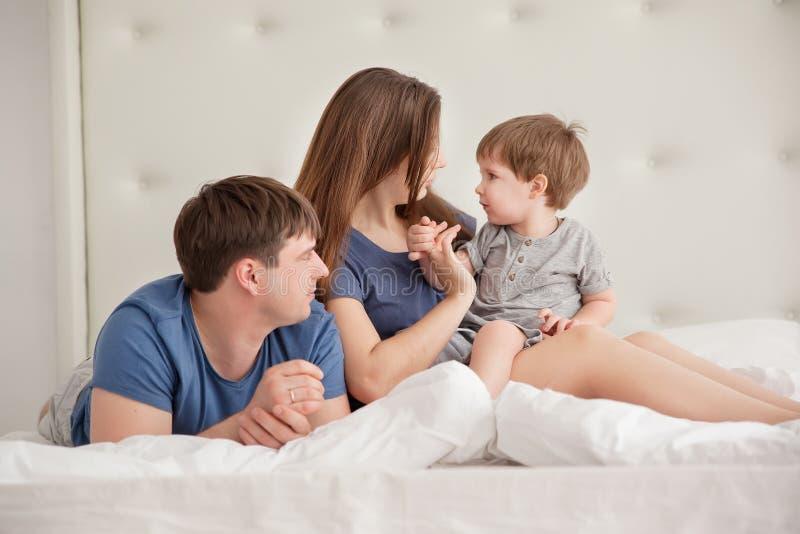Le portrait de famille de trois personnes sur des parents enfoncent les pyjamas de port photographie stock libre de droits