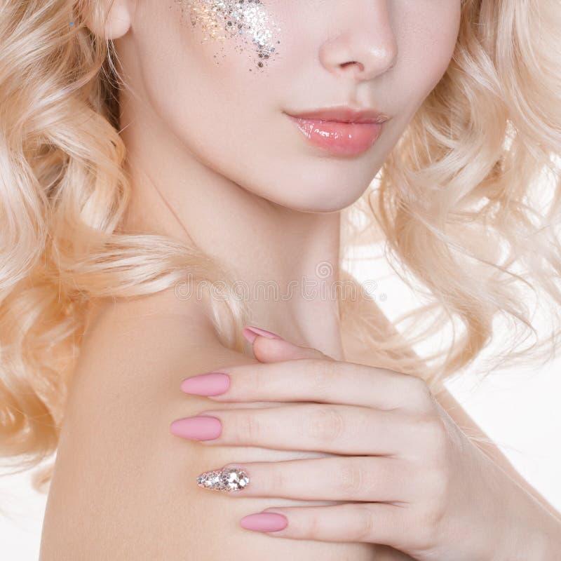 Le portrait de femmes de beauté de la jeune femme blonde bouclée avec la manucure en pastel et l'art parfait préparent avec le sc image libre de droits