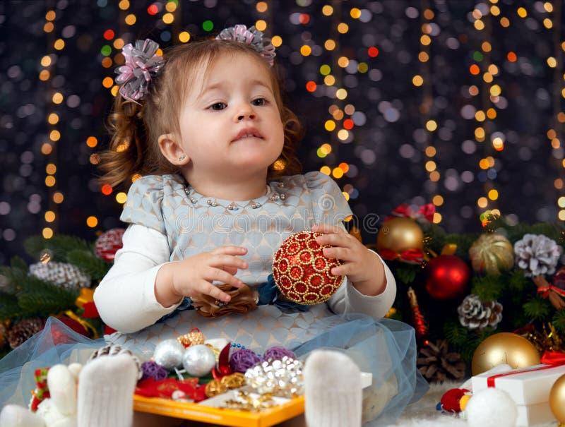 Le portrait de fille à la décoration de Noël avec le cadeau, à l'arrière-plan foncé avec l'illumination et au boke s'allume, conc photographie stock