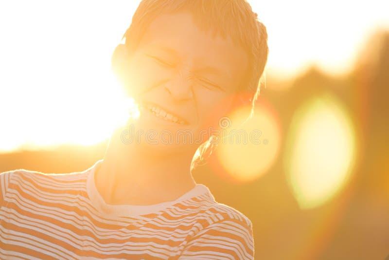 Le portrait de Headshot du vissage vers le haut des yeux riant l'adolescent dans le coucher du soleil chaud éclairé à contre-jour photos stock