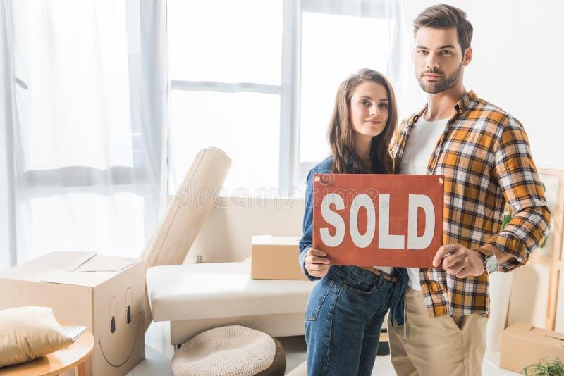 le portrait de jeune se tenir de couples a vendu la carte rouge à la maison photo libre de droits