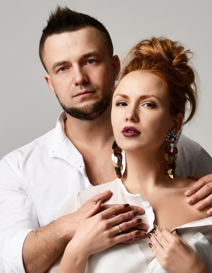 Le portrait de jeunes couples élégants dans la position officielle de vêtements avèrent le fond gris photos libres de droits