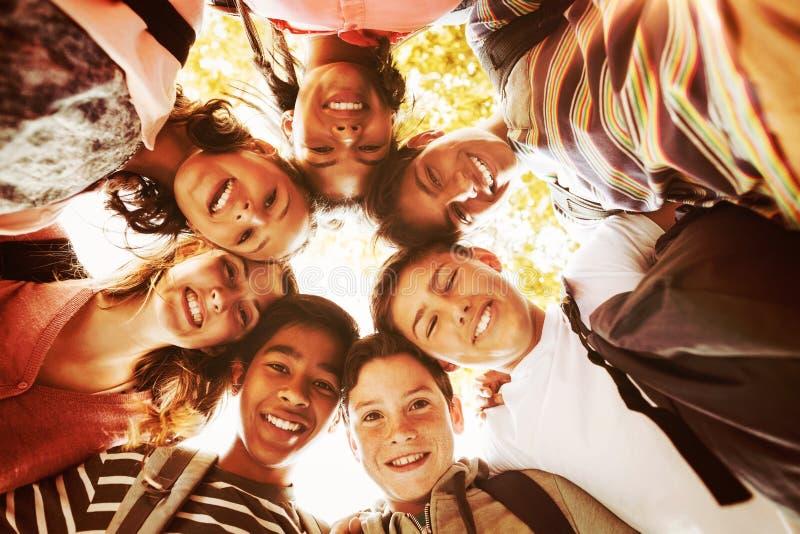 Le portrait de l'école de sourire badine former un petit groupe dans le campus photos libres de droits