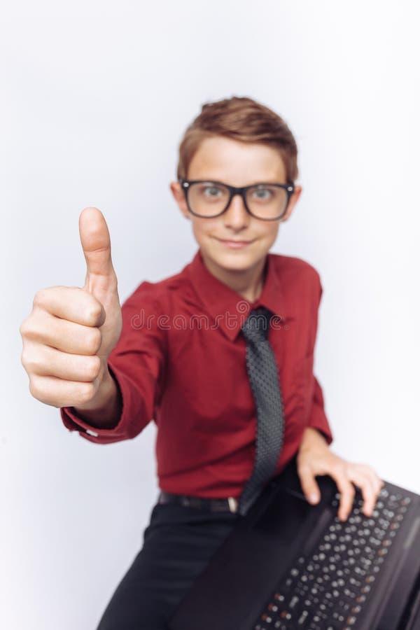 Le portrait de l'écolier positif et émotif posant avec l'ordinateur portable, et montrent la classe, fond blanc, verres, chemise  images stock