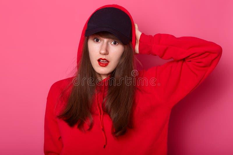 Le portrait de l'adolescent européen étonné de brune maintient sa main sur la tête, supports avec la bouche ouverte, habillée dan image libre de droits