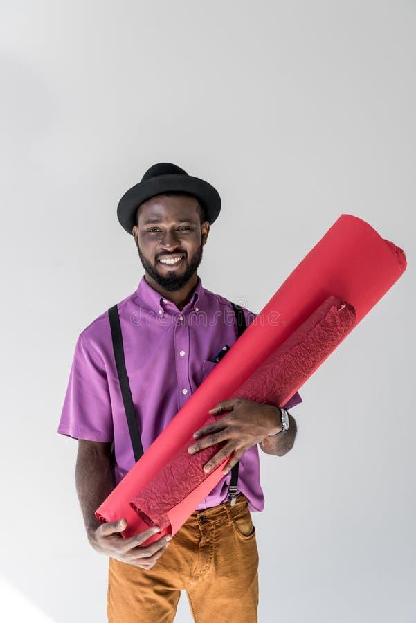 le portrait de l'afro-américain à la mode de sourire dans le chapeau tenant le papier d'emballage rose roule dans des mains photos libres de droits