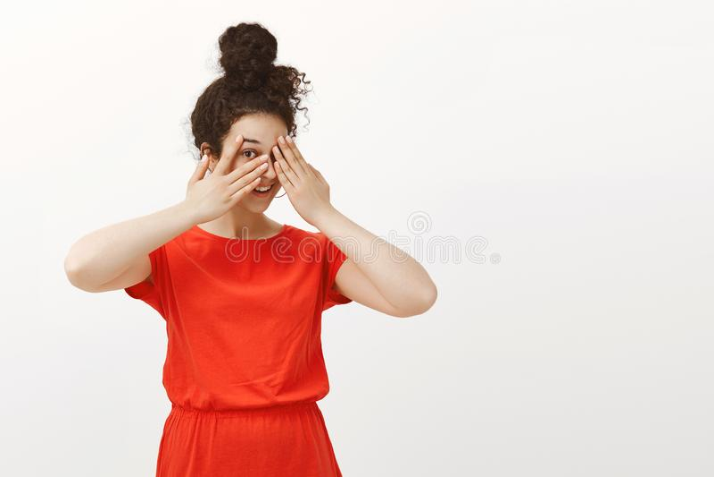 Le portrait de l'amie heureuse espiègle dans la robe rouge mignonne avec les cheveux bouclés peignés en petit pain, couvrant obse images libres de droits