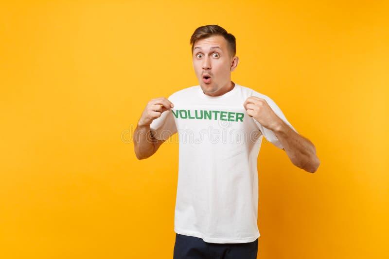 Le portrait de l'amusement a choqué le jeune homme étonné dans le T-shirt blanc avec l'inscription écrite volontaire vert de titr photos libres de droits