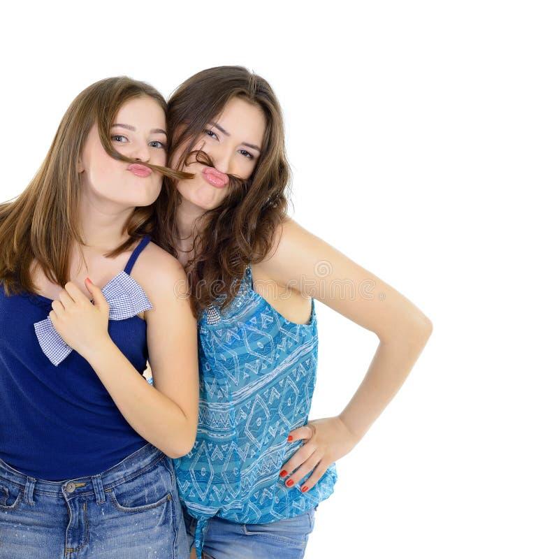 Le portrait de l'deux filles de l'adolescence ont l'amusement et font des visages avec la moustache faite de tresse de cheveux image stock