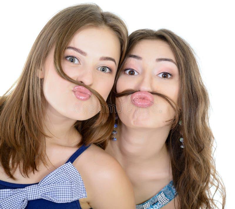 Le portrait de l'deux filles de l'adolescence ont l'amusement et font des visages avec la moustache faite de tresse de cheveux image libre de droits