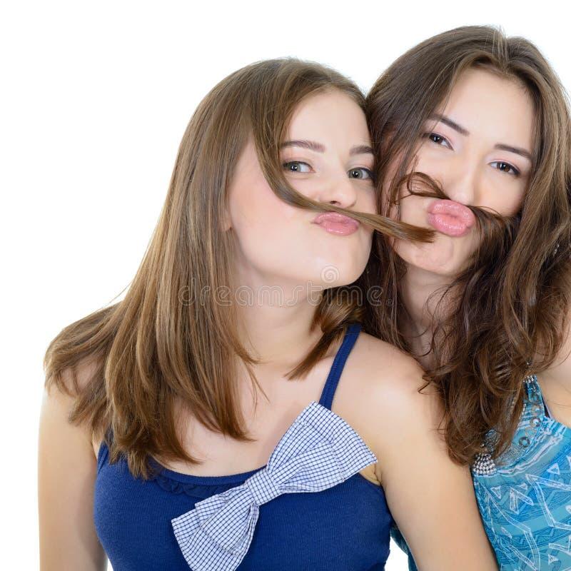Le portrait de l'deux filles de l'adolescence ont l'amusement et font des visages avec la moustache faite de tresse de cheveux photos libres de droits