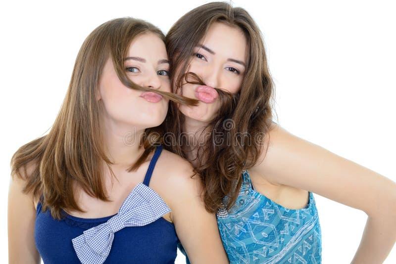 Le portrait de l'deux filles de l'adolescence ont l'amusement et font des visages avec la moustache faite de tresse de cheveux photo stock