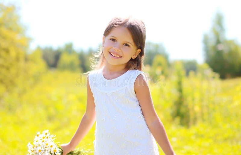 Le portrait de l'enfant de sourire mignon de petite fille avec le bouquet fleurit image stock