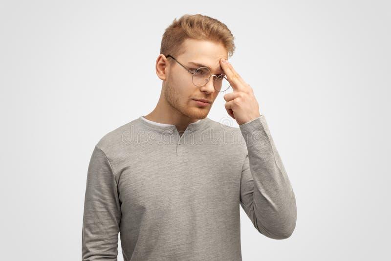 Le portrait de l'entrepreneur masculin songeur garde des doigts sur le front, essaye de se concentrer avant de créer le projet d' image libre de droits
