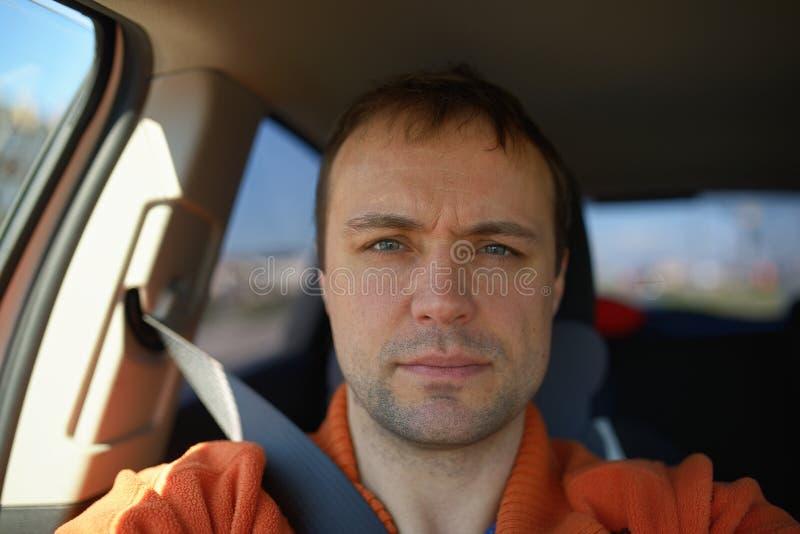 Le portrait de l'homme adulte dans la voiture a attaché par la ceinture de sécurité images stock