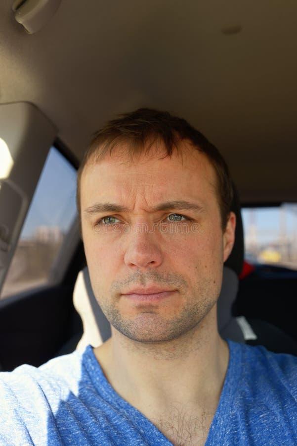 Le portrait de l'homme adulte dans la voiture a attaché par la ceinture de sécurité photographie stock