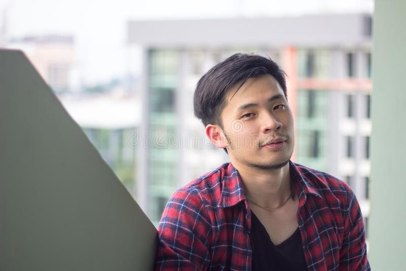 Le portrait de l'homme asiatique bel se repose sur le toit de tour b images stock