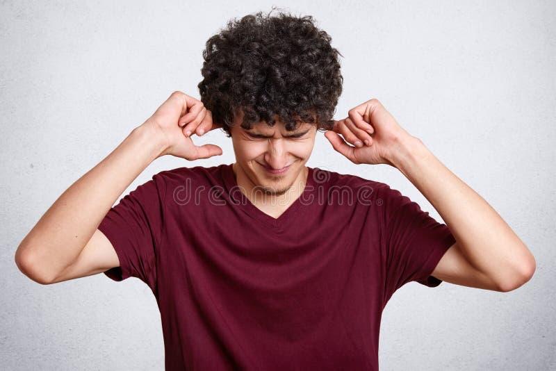 Le portrait de l'homme barbu bel inquiété dans le T-shirt marron occasionnel, se tenant avec les yeux fermés et mettant des doigt image libre de droits
