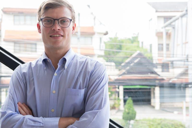 Le portrait de l'homme d'affaires avec des bras a croisé au bureau jeune homme s image libre de droits