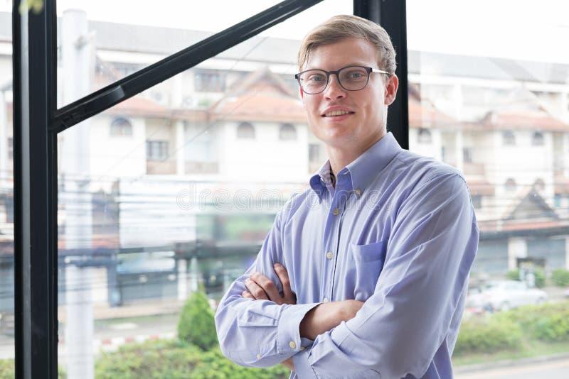 Le portrait de l'homme d'affaires avec des bras a croisé au bureau jeune homme s photographie stock