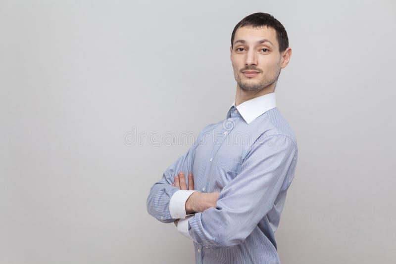 Le portrait de l'homme d'affaires bel de poil dans la position bleu-clair classique de chemise, a croisé des mains et regarder la image libre de droits