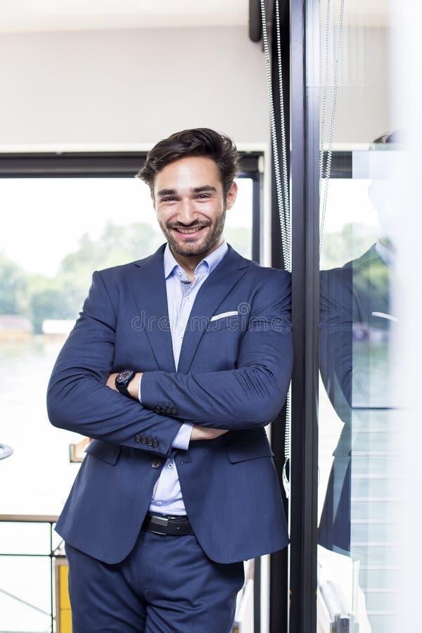 Le portrait de l'homme d'affaires heureux avec des bras a crois? la position dans le bureau images libres de droits