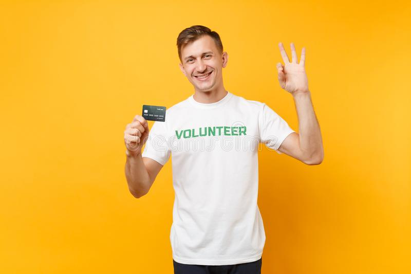 Le portrait de l'homme dans le T-shirt blanc avec le titre écrit de vert d'inscription la prise volontaire carte de banque dispon photographie stock libre de droits