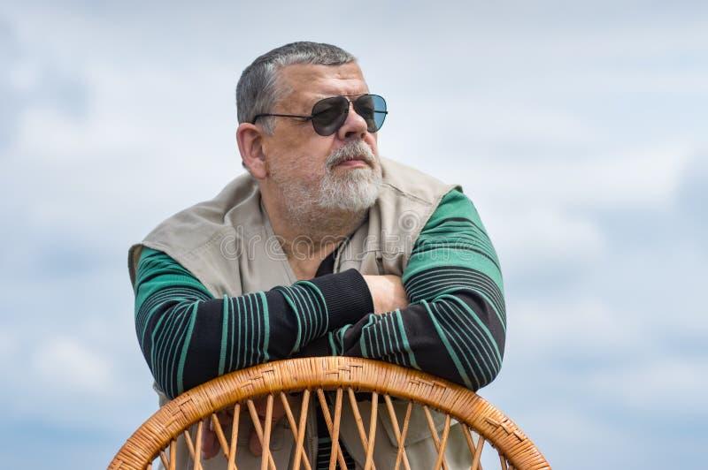Le portrait de l'homme supérieur dans des lunettes de soleil noires s'est penché sur un dos et un regard de chaise en osier image libre de droits