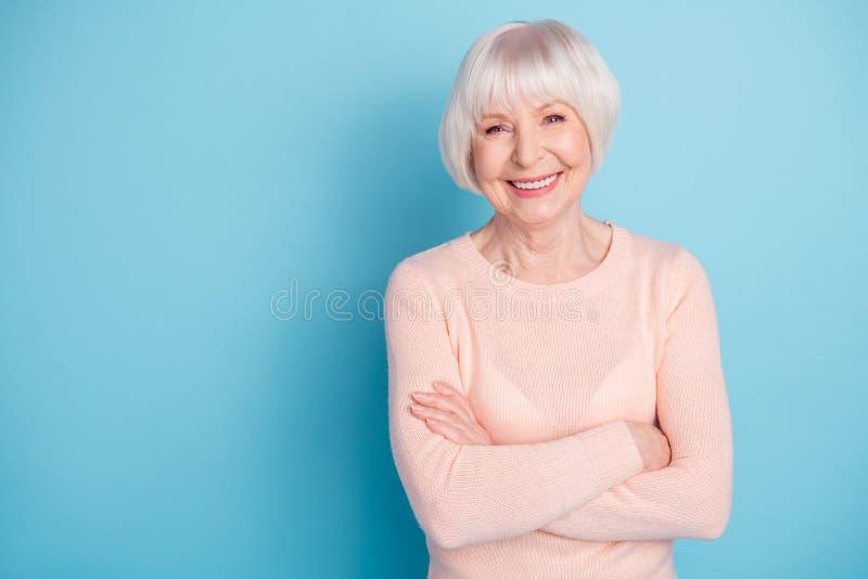 Le portrait de la belle dame avec ses bras a plié avoir le sourire toothy utilisant le chandail en pastel d'isolement au-dessus d image libre de droits