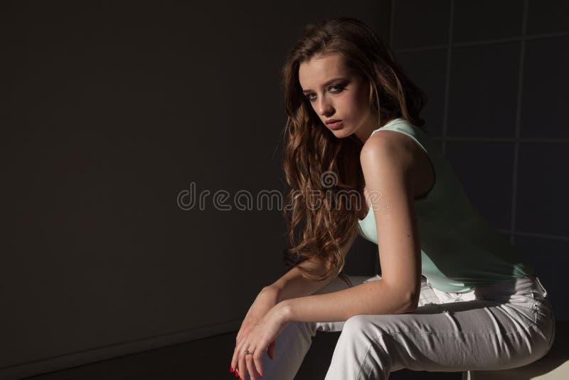 Le portrait de la belle femme à la mode dans des vêtements lumineux se repose image stock