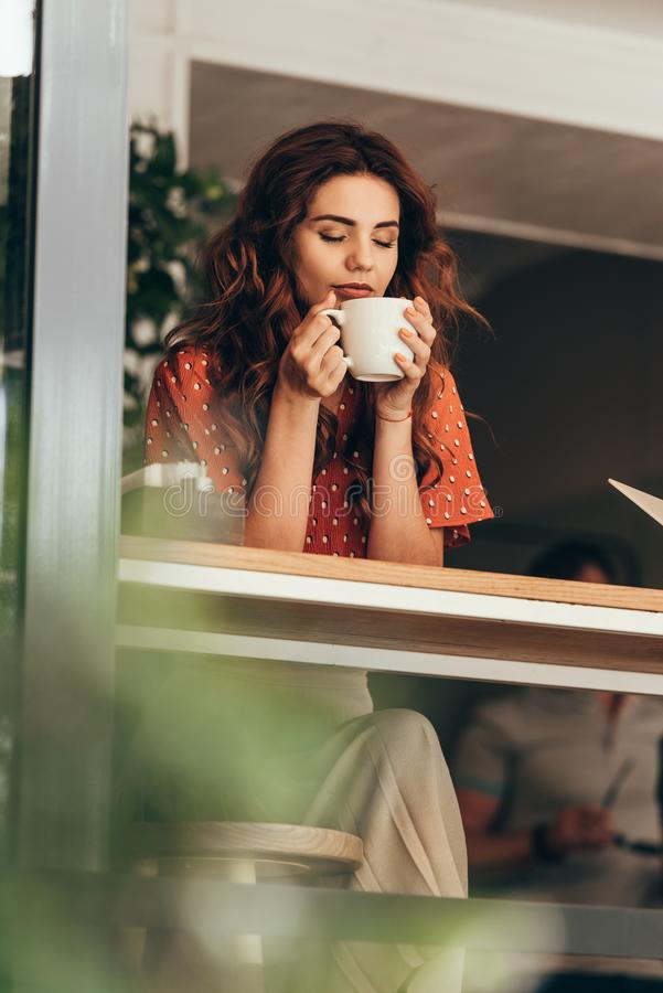 le portrait de la belle femme avec l'oeil a clôturé tenir la tasse de café aromatique dans des mains photos libres de droits