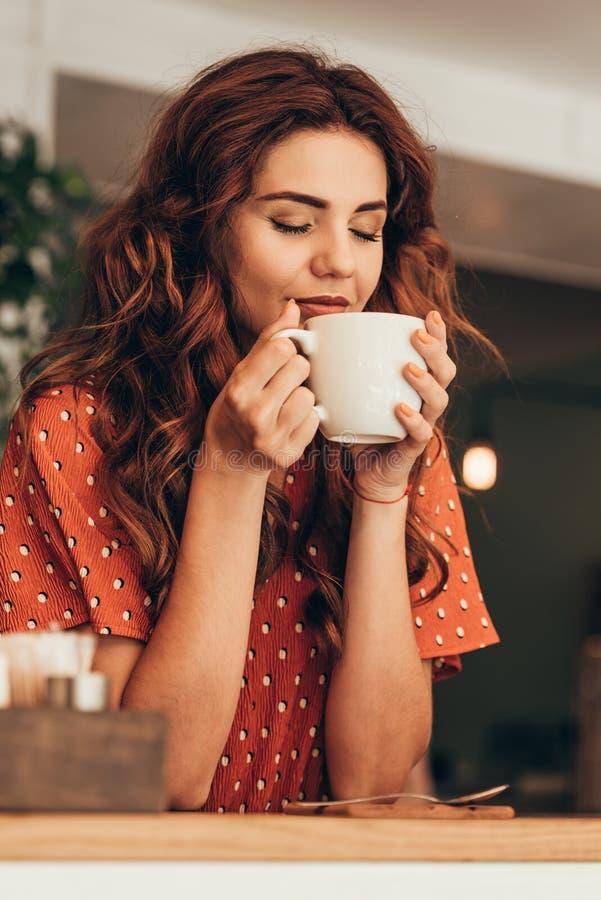 le portrait de la belle femme avec l'oeil a clôturé tenir la tasse de café aromatique dans des mains images libres de droits