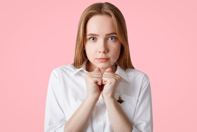 Le portrait de la belle femme focalisée sérieuse maintient des mains dans les poings, utilise la chemise blanche, a l'espoir pour images stock