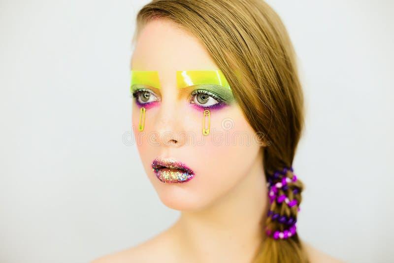 Le portrait de la belle fille avec créatif composent avec des scintillements photographie stock libre de droits