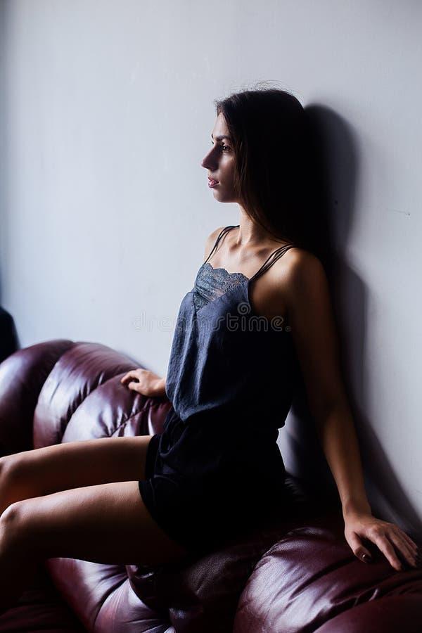 Le portrait de la belle fille avec le maquillage et les longs cheveux de brune porte les vêtements à la maison photographie stock libre de droits