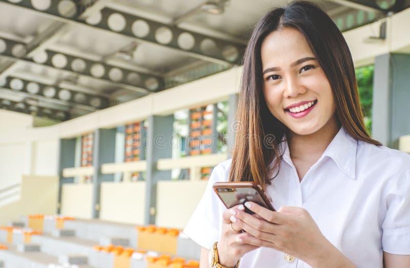 Le portrait de la belle fille d'étudiant d'uniforme adulte thaïlandais d'université apprécie des médias sociaux sur son smartphon photos stock