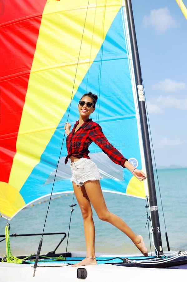Le portrait de la belle fille de brune tient des voiles et le sourire de bateau photos stock