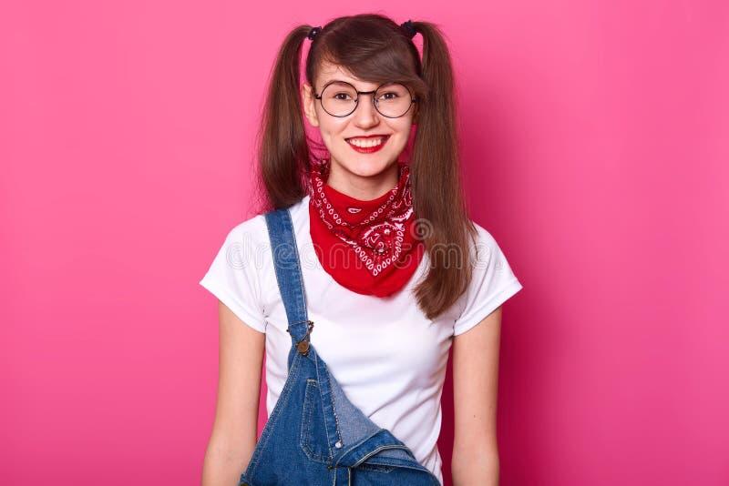 Le portrait de la belle fille gaie avec de longs tresses, porte le T-shirt, les combinaisons de denim et le bandana rouge sur le  image libre de droits