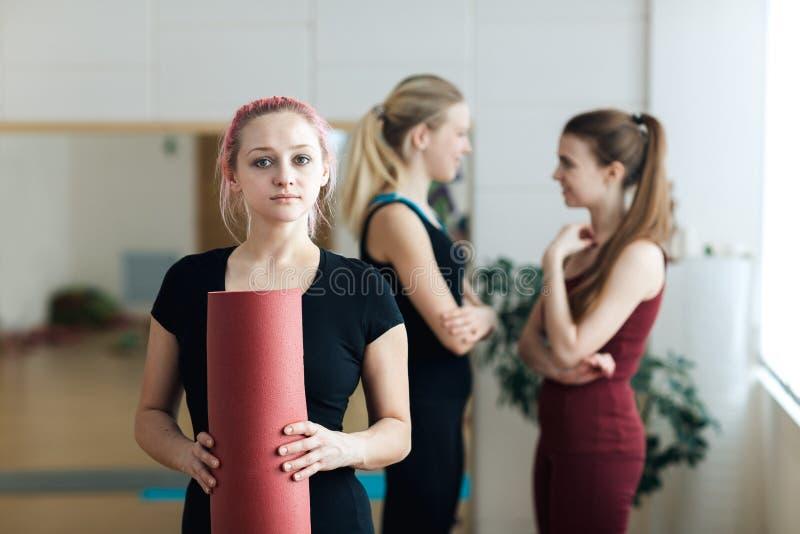 Le portrait de la belle fille heureuse de yogi avec la participation rose de cheveux a plié le tapis rouge de yoga après leçon s' photo stock