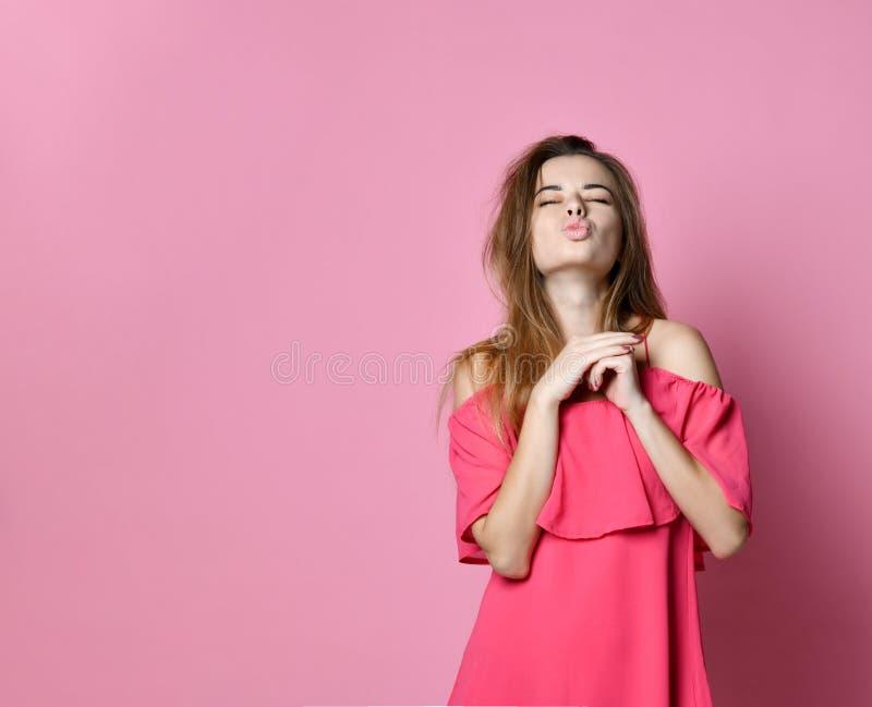 Le portrait de la belle fille mignonne dans des lèvres roses de tacauds de robe, envoie des baisers à la caméra, photo stock