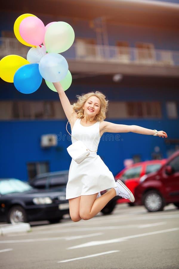 Le portrait de la belle jeune blonde saute du bonheur tenant des ballons image libre de droits