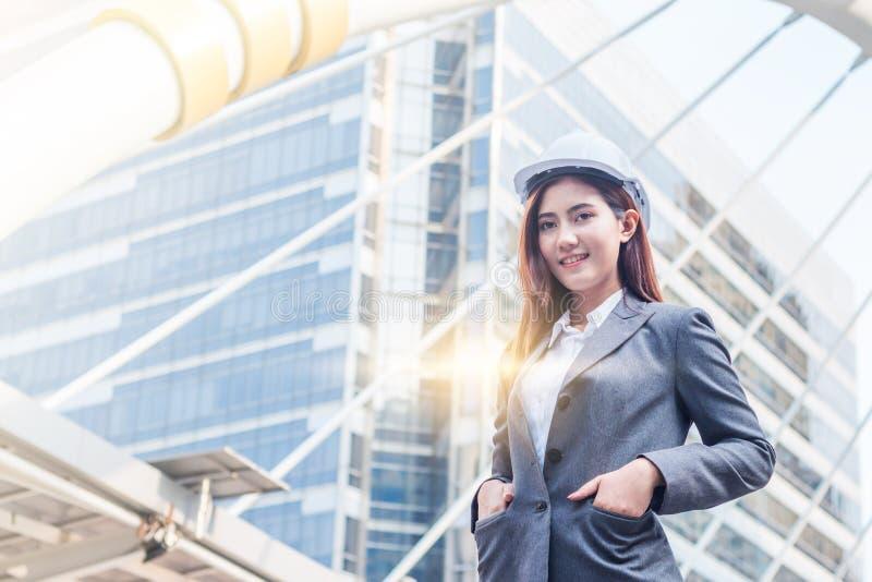 Le portrait de la belle jeune femme d'ingénieur portent un casque de sécurité blanc souriant avec l'engagement au succès au centr images libres de droits