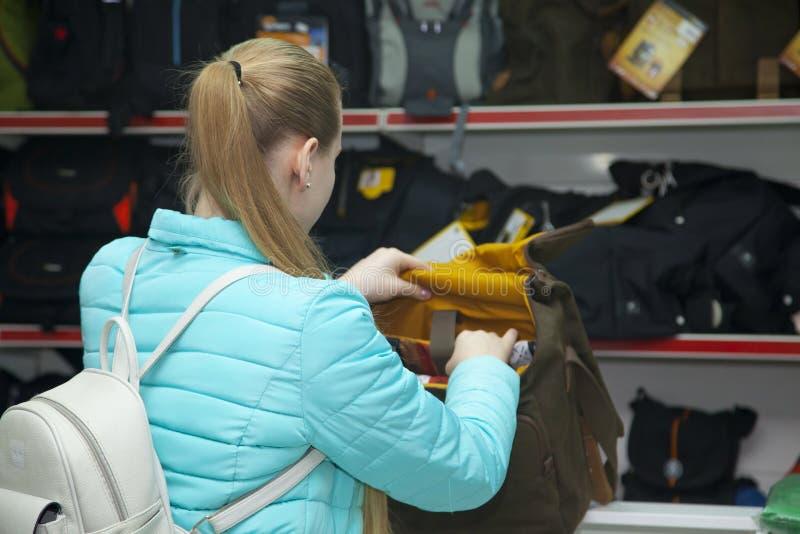 Le portrait de la belle jeune fille blonde dans le magasin professionnel d'équipement de photo choisit le sac à dos pour la camér image stock