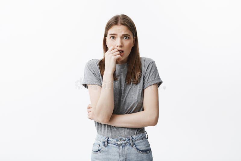Le portrait de la belle jeune fille européenne malheureuse d'étudiant avec les cheveux foncés et des yeux bruns dans des vêtement photos stock
